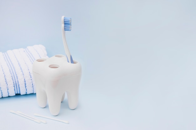 Toothbrush; cotton swab and towel on blue background Free Photo