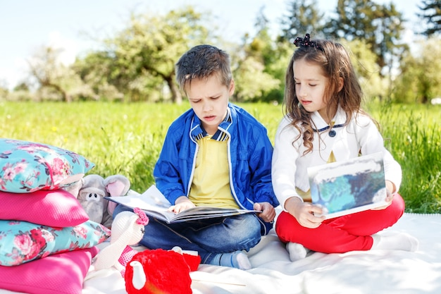 Two children read books in the park. concept of education Premium Photo