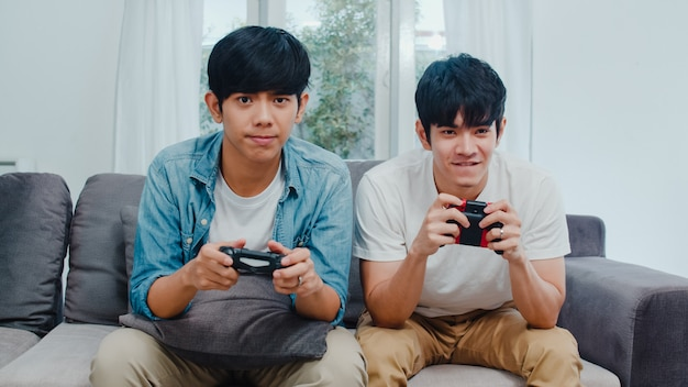 Young asian gay couple play games at home. teen korean lgbtq+ men using joystick having funny happy moment together on sofa in living room at ...