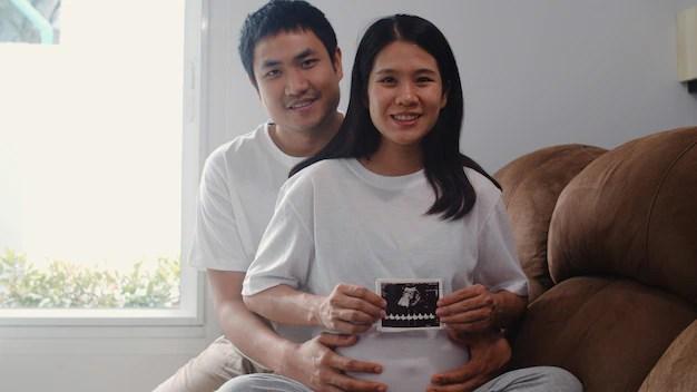 Casal de asiáticos segurando a foto do ultrassom na barriga da esposa.