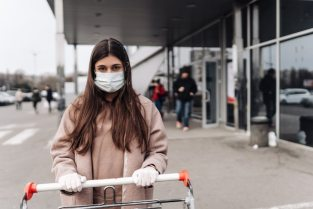 Young woman wearing protection face mask against coronavirus 2019-ncov pushing a shopping cart. Free Photo