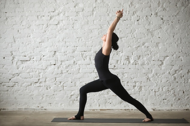 Young yogi attractive woman in Warrior one pose, loft background Free Photo