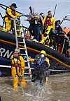 Immigration Enforcement officers and members of the RNLI assist a group of people thought to be migrants from an RNLI lifeboat.
