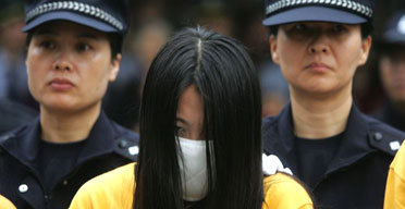 Chinese police escort a woman during a public shaming