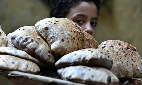 A child carries a tray of bread in Cairo