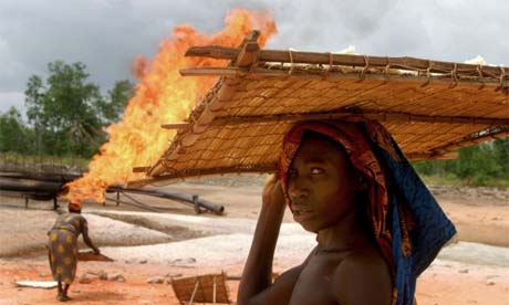 Women dry tapioca beside flames from Shell's Utorogu flow station in the Niger Delta March 5, 2006