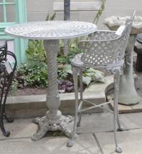 Tall white metal outdoor table with single chair