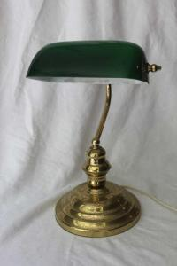 A brass desk lamp with green glass shade
