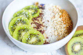 Auf diesem Bild ist eine Kiwi - Haferflocken Frühstücksbowl auf einer weißen Marmorplatte zu sehen.
