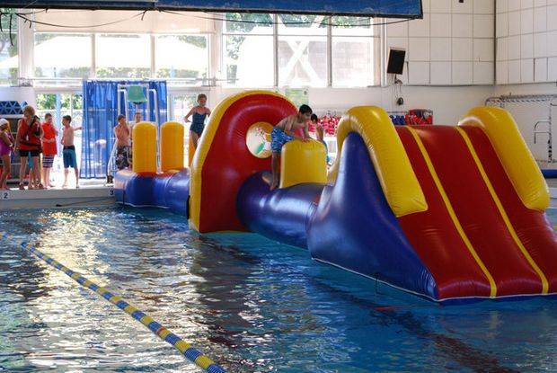Wipeout Kids slip slide across giant floating inflatable
