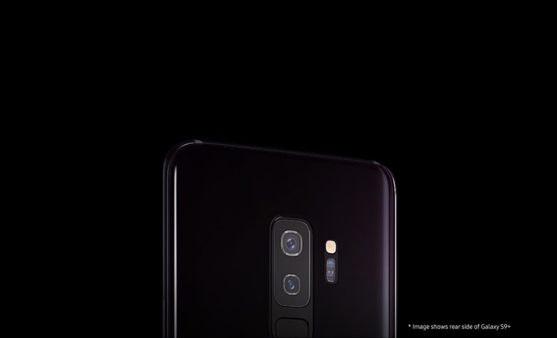 Soft lit against a dark backdrop, the rear side view of a Lilac Purple Galaxy S9+ emphasizes the dual camera and rear hardware, and sleek body design.