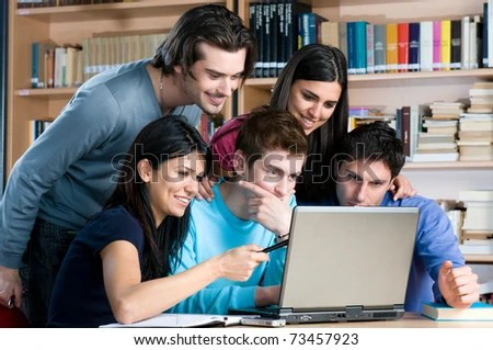 stock photo : Absorbed young students watching at laptop and study together at college library