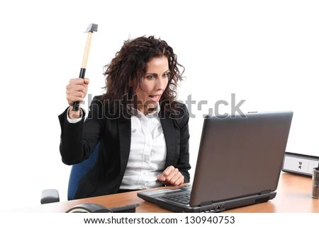 Mature businesswoman trying to destroy a laptop with a hammer in an office on a white isolated background - stock photo