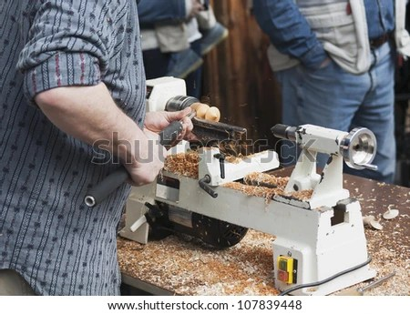 Man Carving A Wooden Spinning Top With Machine Stock Photo