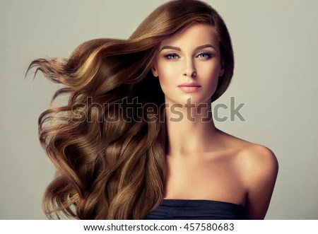 brunette girl with long and shiny wavy hair beautiful model with curly hairstyle stock photo