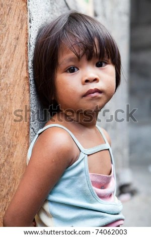 Image of a young girl leaning on a post in the Philippine rural area