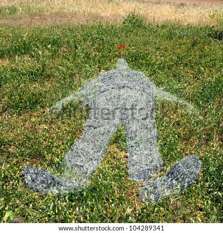 Withered grass ghostlike human figure imprint on green field. - stock photo