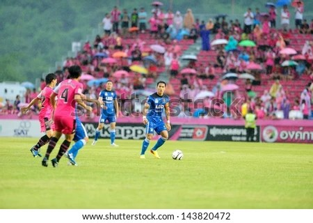 CHAINAT,THAILAND JUNE 2013 : Teeratep Winothai (blue,14) in action during a geam Thai premier League 2013 between Bangkok Glass FC and Chainat F.C. at Khao Plong Stadium on June 22, 2013 in Thailand - stock photo
