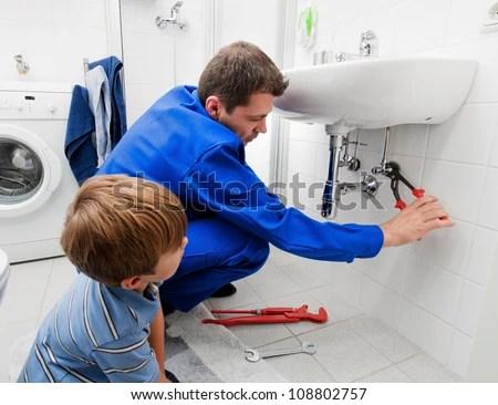 A Plumber Repairing A Broken Sink In Bathroom Stock Photo