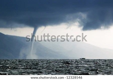 stock photo : Boat running away from a tornado in stormy sea