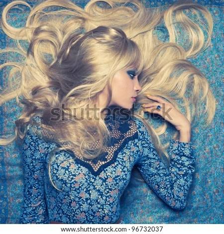 Beautiful sensual blonde lying on a blue pattern - stock photo