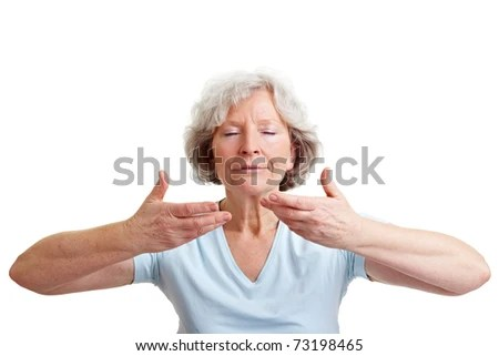 Relaxed senior woman doing some breathing exercises - stock photo