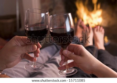 stock photo : Feet warming at fireplace with hands holding wine