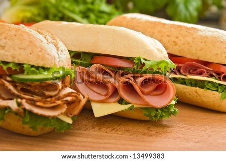 stock photo : Three fresh sandwiches - turkey breast, ham & swiss and salami on a cutting board. Focus on the ham sandwich