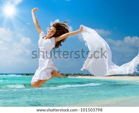 Όμορφο κορίτσι άλματα στην παραλία.  Concept για διακοπές - φωτογραφία απόθεμα