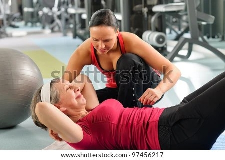 stock photo : Fitness center senior woman exercise with personal trainer on mat