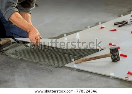 ceramic tiles tiler placing ceramic wall tile in position over adhesive with lash tile leveling system stock images page everypixel