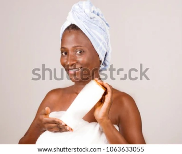 Young African Girl Standing In Bath Towel Showing A Tube Of Ointment Smiling