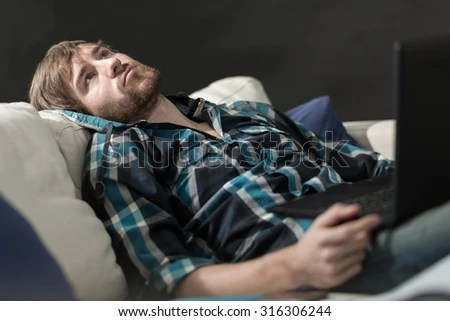 Bored man with a laptop on the couch