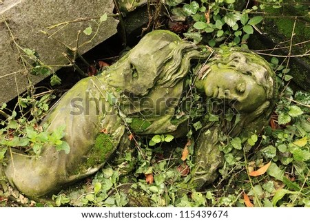 Forgotten sleeping young stone girl laying in green nettles - stock photo