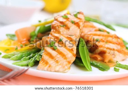 stock photo : grilled salmon with spring vegetables on white plate, soft focus