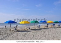 Row Of Beach Chairs And Umbrellas Waiting For Sunbathers ...