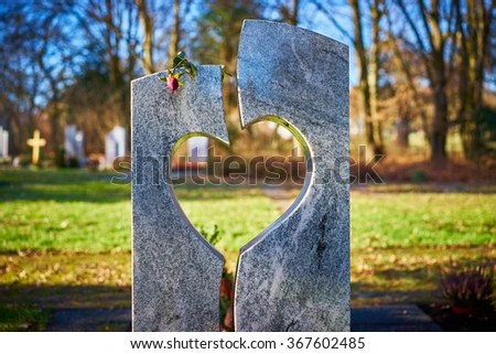 Tombstone with heart and rose / Gravestone with heart and withered rose on graveyard / Sorrow about loss of beloved ones