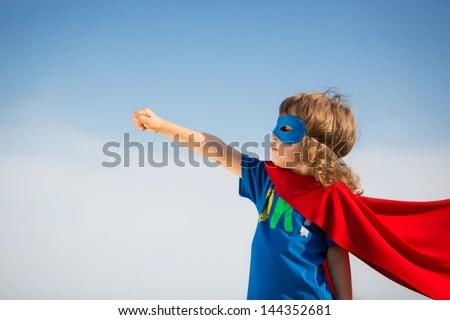 Superhero kid against blue sky background. Girl power concept - stock photo