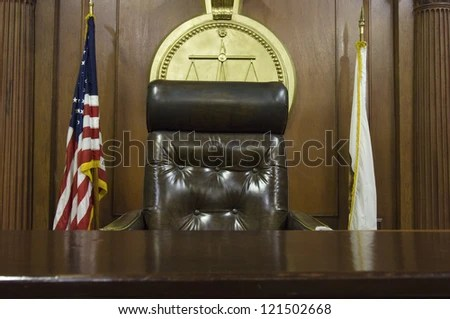 Chair Of Judge And Flags In Empty Courtroom Stock Photo