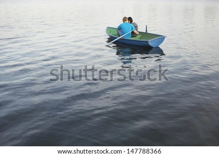 Rear view of a loving young couple cuddling in rowboat at lake - stock photo