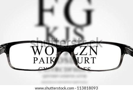 Sight test seen through eye glasses, white background isolated - stock photo
