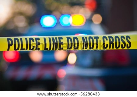 stock photo : Shallow depth of field image taken of yellow law enforcement line with police car and lights in the background.