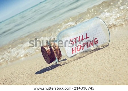 "Message in a bottle ""Still hoping"" on sandy beach. Creative hope and faith concept.  - stock photo"