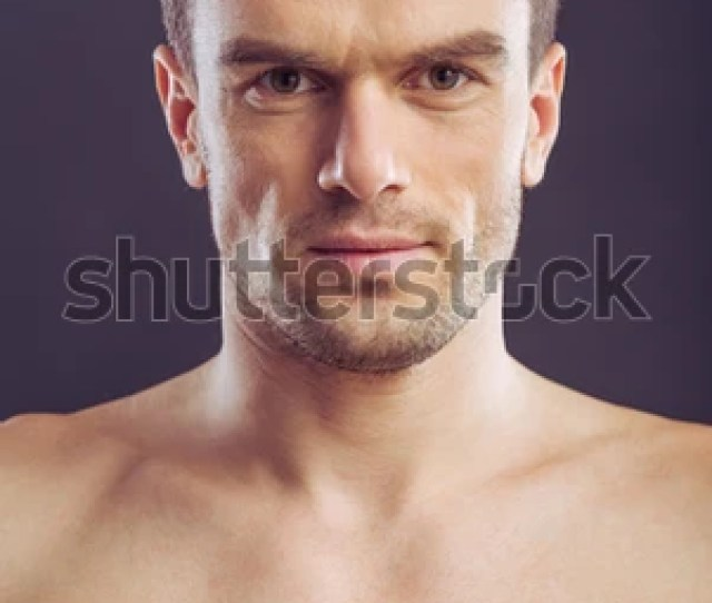 Portrait Of Handsome Naked Man Looking At Camera On A Dark Background Close Up