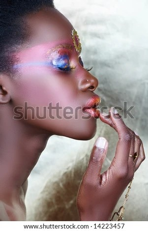 stock photo : Beautiful African woman with metallic bronzed tribal make-up and closed eyes, touching her lips