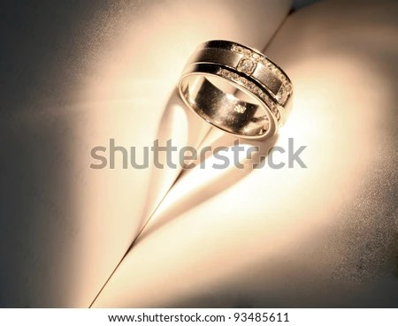 """stock photo : Wedding Luxury Diamond ring casting a heart on Book Using for """"Love never ends"""" Concept in Valentine Holiday"""