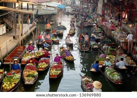 RATCHABURI,THAILAND-JAN 2013  : Local peoples sell fruits,food and products  at Damnoen Saduak floating market,on Jan 1,2013 in Ratchaburi,Thailand.Dumnoen Saduak is a very popular tourist attraction. - stock photo