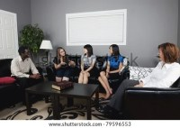 A Group Of People Talking In A Living Room Stock Photo