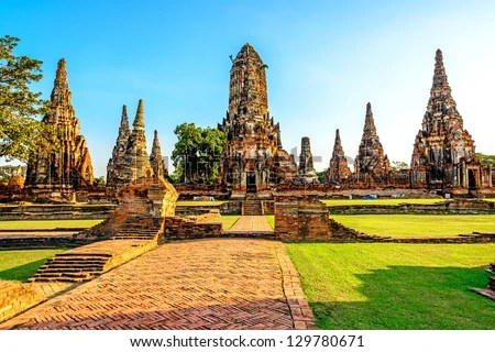 The Buddhist stupas of Wat Chai Watthnaram temple viewed from entrance in Ayutthaya, Thailand at early-evening. - stock photo