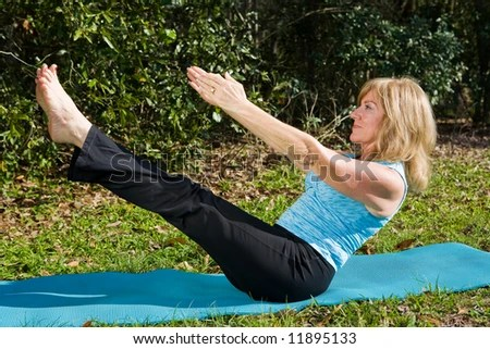 Amazingly fit and beautiful mature woman doing an advanced pilates move. - stock photo